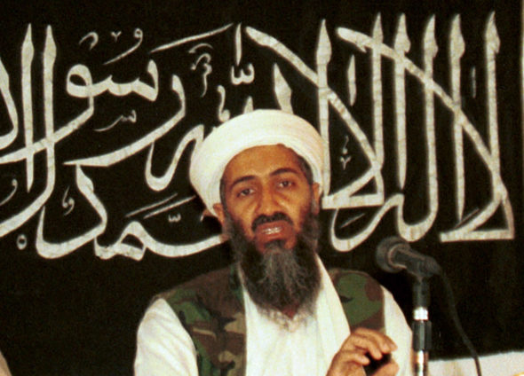 """In this 1998 file photo made available on March 19, 2004, Osama bin Laden is seen at a news conference in Khost, Afghanistan. Bin Laden, was on the FBI's Ten Most Wanted Fugitives list before the terrorist attacks of 9/11, put there for his role in the 1998 deadly bombings of U.S. Embassies in Tanzania and Kenya, appearing as Usama bin Laden. When he was killed in 2011, the FBI updated the list to include a large red-and-white """"deceased"""" label atop his photograph. (AP Photo/Mazhar Ali Khan, File)"""