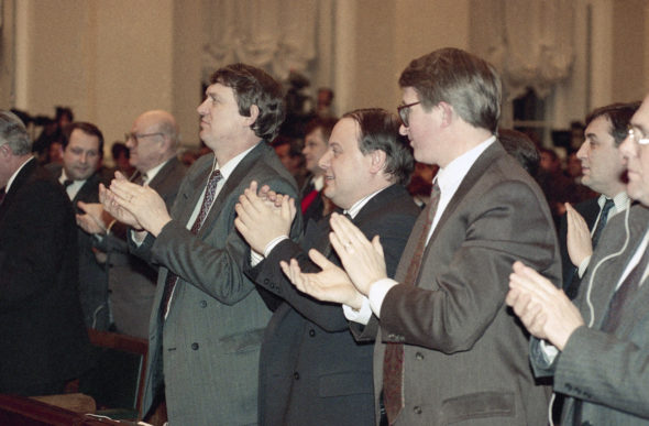 First Vice Premier Vladimir Shumeiko, right, Acting Prime Minister Yegor Gaidar, second from right, Vice Premier Alexander Shohin, second from left, among other member's of the Cabinet applaud as they watch screen displaying the vote results as the Congress of Russian Peoples approved its agreement with President Boris Yeltsin 541-98 in the Kremlin, Moscow on Saturday, Dec. 12, 1992. (AP Photo/Dmitry Donskoy)