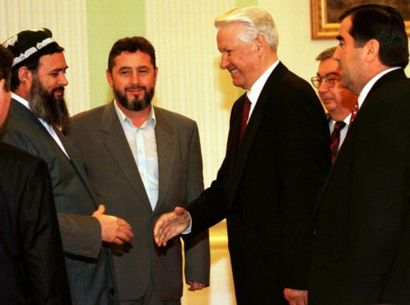 Russian President Boris Yeltsin smiles as he shakes hands with Tajik opposition leader Said Abdullo Nuri, left, in Moscow's Kremlin, Friday, June 27, 1997. Tajikistan President Imomali Rakhmomov, right, and Nuri signed a landmark peace pact Friday designed to bring a formal end to five years of bitter civil war in the Central Asian nation. Nuri's deputy Khodzhi-Akbar Turandzhonzoda, second from left, and Russian Foreign Minister Yevgeni Primakov, second from right, both smile. (AP Photo/ POOL)
